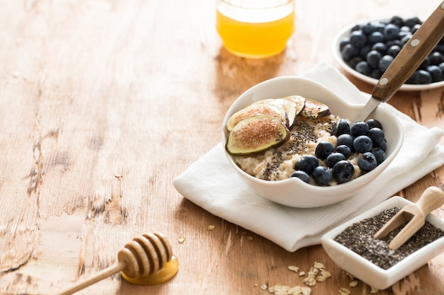 White bowl of oats porridge with figs, blueberries and chia seeds.
