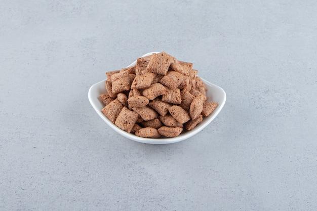 チョコレートの白いボウルは、石の背景にコーンフレークをパッドします。高品質の写真