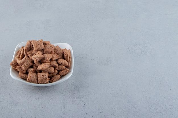 돌 배경에 초콜릿 패드 콘플레이크의 흰색 그릇. 고품질 사진