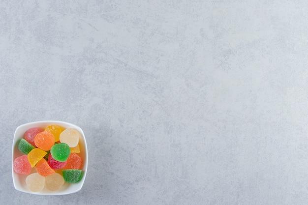 Белая чаша красочных мармеладов желе на мраморной предпосылке.