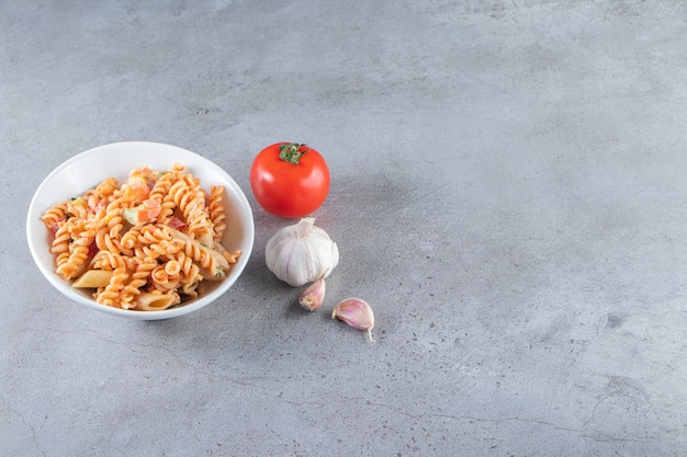 돌 배경에 맛있는 푸실리 파스타의 흰색 그릇.