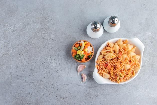 Белая миска вкусных макаронных изделий и миска овощного салата на каменном фоне.
