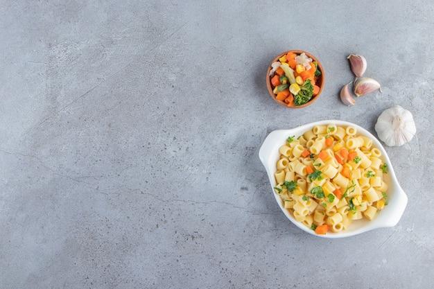 Белая чаша вкусных макарон со свежим салатом на каменном фоне.
