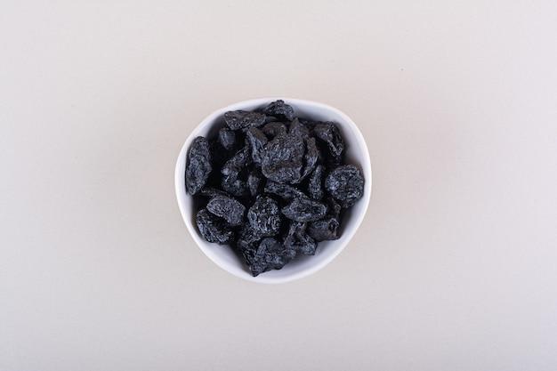 말린 자두 과일의 흰색 그릇은 흰색 표면에 배치됩니다. 고품질 사진