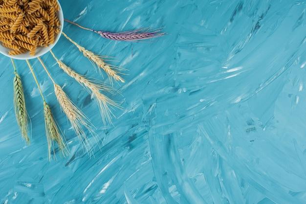 Белая чаша сухих макаронных изделий фузилли с колосьями пшеницы на синем фоне.