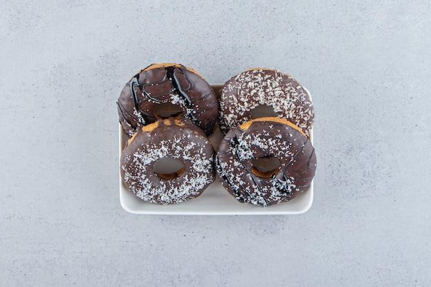 돌 배경에 4개의 초콜릿 도넛이 있는 흰색 그릇. 고품질 사진