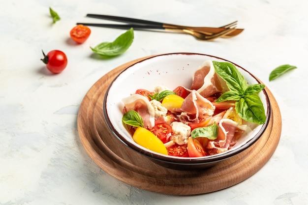 토마토, 크림 치즈 볼, 프로슈토 잼, 바질 잎을 곁들인 신선하고 건강한 지중해식 샐러드의 흰색 그릇. 맛있는 균형 잡힌 음식 개념.