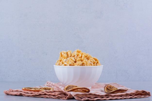 石のテーブルにナッツとハードキャンディーの白いボウル。