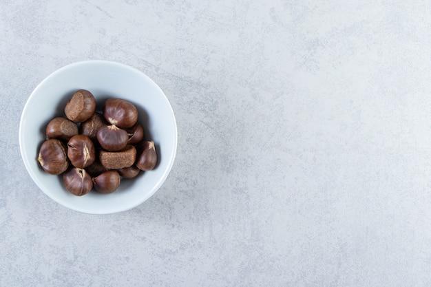 돌 배경에 많은 바삭바삭한 밤의 흰색 그릇.