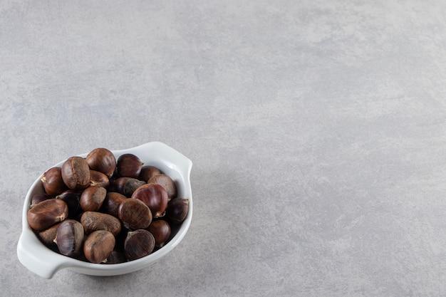 Белая чаша органических очищенных каштанов на каменном фоне.