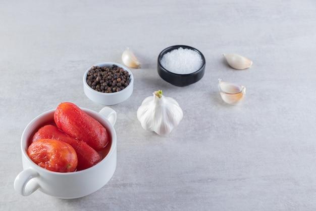 石のテーブルの上に置かれたトマトのピクルスの白いボウル。