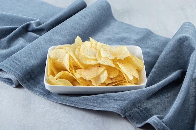 돌에 소금에 절인 감자 칩의 흰색 그릇입니다.