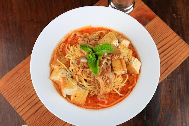 Белая тарелка супа со спагетти и кусочками хлеба, украшенными зеленью