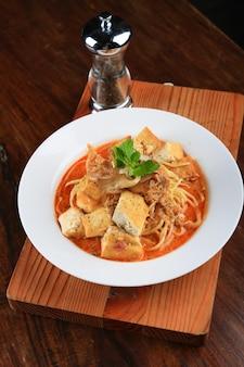 스파게티와 채소로 장식 된 빵 조각이 들어간 흰색 수프 그릇