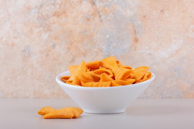 대리석 배경에 삼각형 칩의 흰색 그릇입니다. 고품질 사진