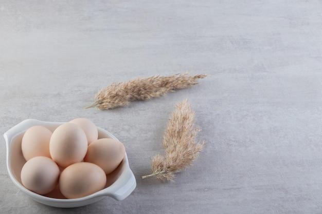 Белая чаша белых сырых яиц на каменном столе.