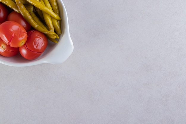 White bowl of pickled tomatoes and peppers on stone table.