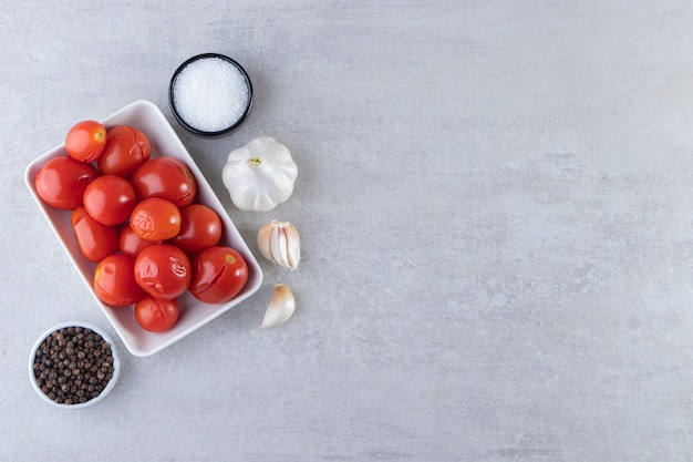 White bowl of pickled tomatoes placed on stone background.
