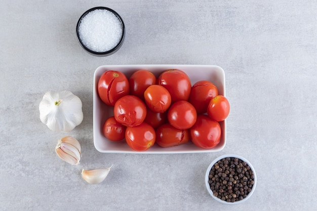 White bowl of pickled tomatoes placed on stone surface.