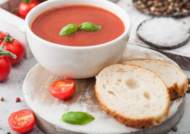 White bowl plate of creamy tomato soup with spoon on light table with box of raw tomatoes and bread. macro