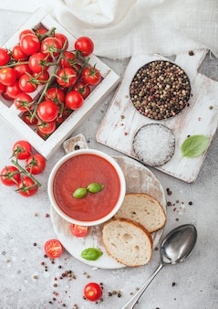 White bowl plate of creamy tomato soup with spoon on light table with box of raw tomatoes and bread. top view