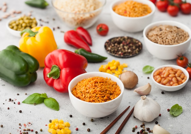 明るい背景に野菜とマッシュルームを添えた長粒バスマティライスとコーン、ニンニク、バジルと豆とエンドウ豆を添えたパプリカペッパーを添えた白いボウルプレート。