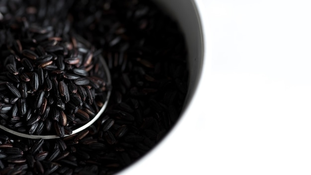 White bowl of raw black rice