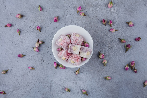 White bowl of rose delights with nuts on stone surface.