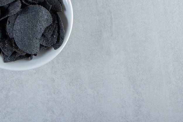 White bowl of salted crispy black chips on stone.