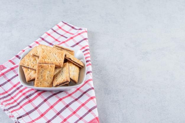 White bowl of tasty crispy crackers on stone.