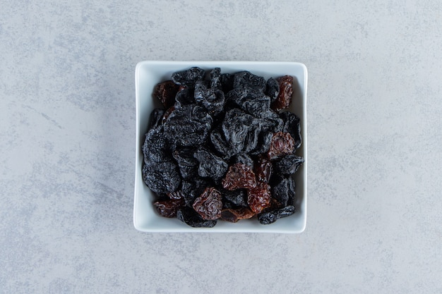 White bowl of tasty dried dates on stone background.