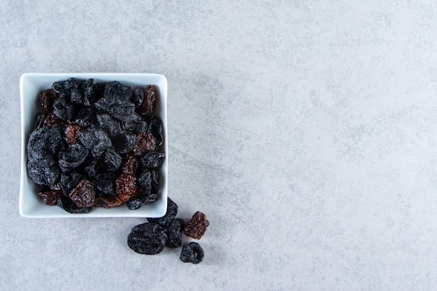 Ciotola bianca di gustosi datteri secchi su pietra.