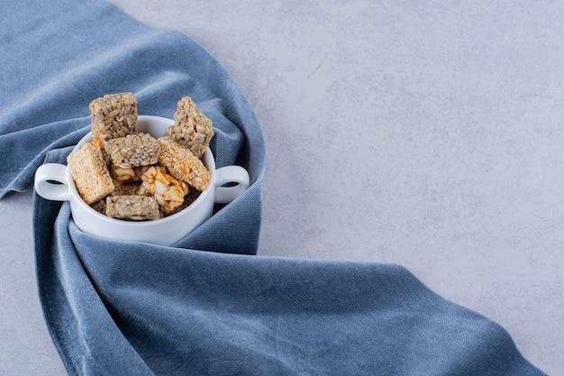 Ciotola bianca di varie caramelle dure con noci sul tavolo di pietra.