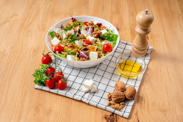 White bowl of vegetarian salad with iceberg lettuce with a mix of healthy ingredients such as walnuts, cherries tomatoes, walnuts, carrots, fresh cheese and corn. top view..