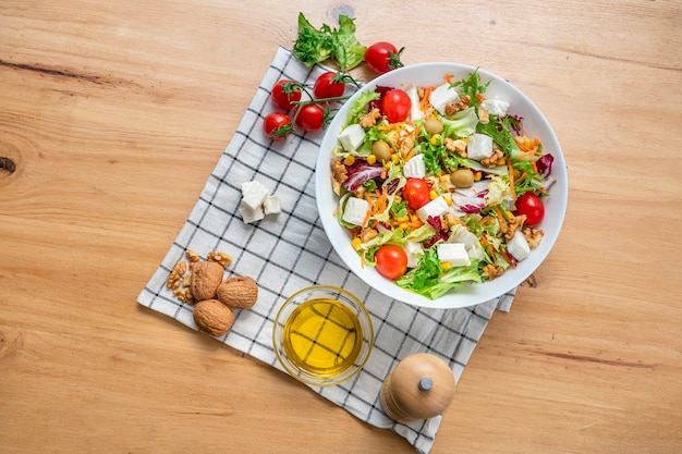 White bowl of vegetarian salad with iceberg lettuce with a mix of healthy ingredients such as walnuts, cherries tomatoes, walnuts, carrots, fresh cheese and corn. top view