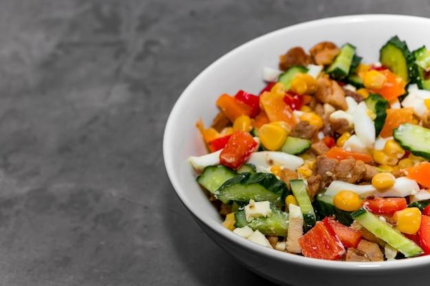 灰色の暗い背景に野菜と鶏肉の明るいサラダと白いボウル