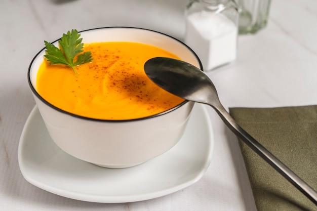 スカッシュとニンジンのスープのクリームと白いボウル水平フレーム