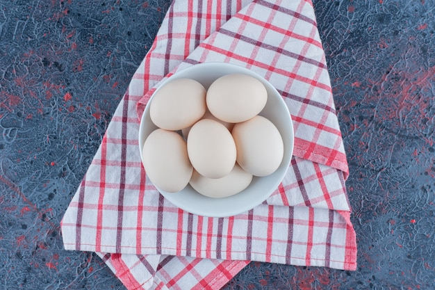 A white bowl with fresh raw chicken eggs .