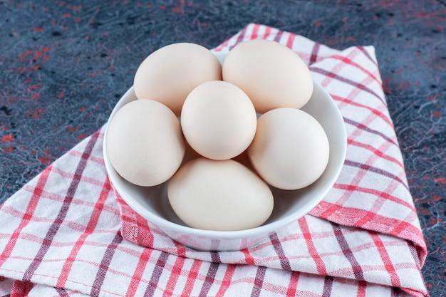 Una ciotola bianca con uova di gallina fresche crude