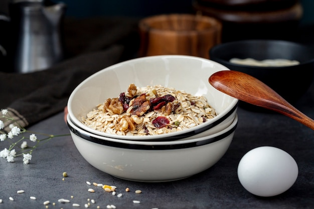 White bowl with musli and a wooden spoon with an egg on a grey background