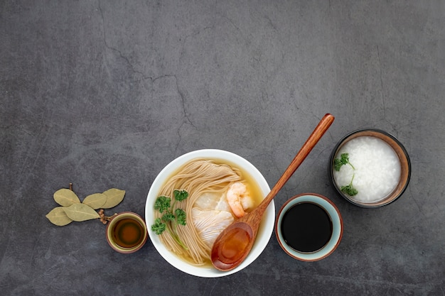 White bowl with noodle soup on a grey background