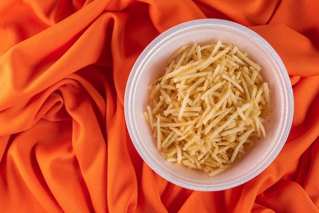 オレンジ色の背景にジャガイモわらと白いボウル