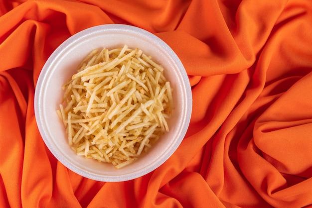 Белая миска с картофельной соломкой на оранжевой поверхности