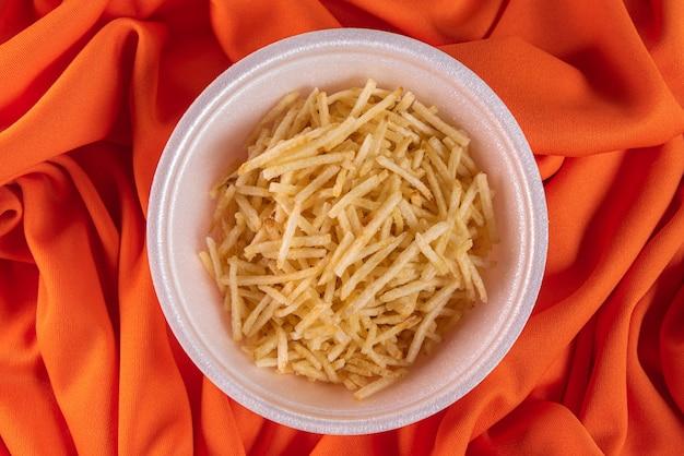 オレンジ色の表面にジャガイモのわらが付いている白いボウル
