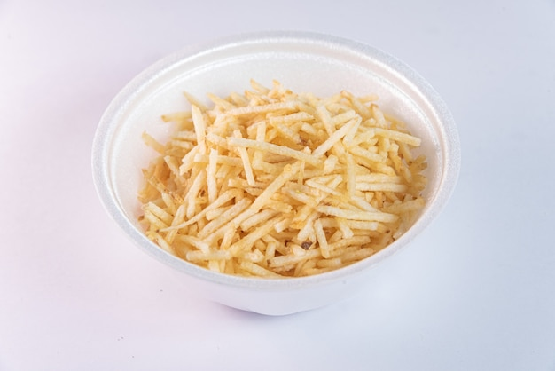 White bowl with potato straw on white background