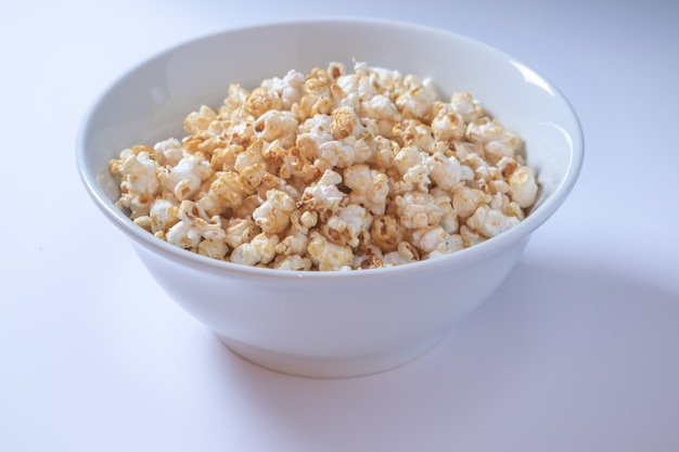 Белая миска со сладким попкорном на белом фоне