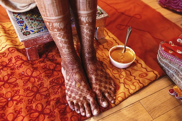 White bowl with turmeric paste stands beneath indian bride