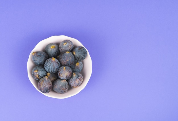 White bowl with whole ripe figs on a blue background copy space