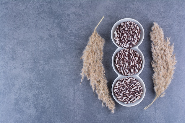 Ciotole bianche di biscotti con sciroppo di cioccolato su una pietra.