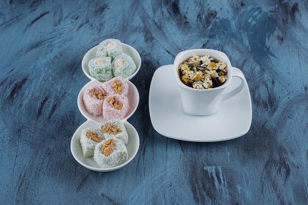 Белые чаши различных сладостей с орехами и чаем на синей поверхности.